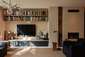 Bookshelves, TV and low sideboard next to fireplace with firewood store in living room