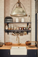 Storage jars on shelves on tiled wall above kitchen counter with integrated sink and wooden worksurface