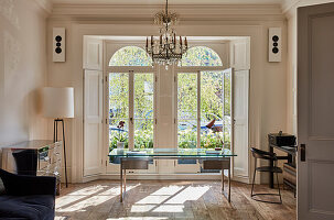 Glass table below chandelier in bright study with Victorian French windows