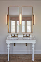 Vintage-style washstand with twin sinks, two mirrors and three wall lamps in bathroom