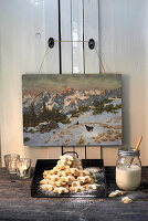 Pile of cinnamon stars under old painting of winter landscape
