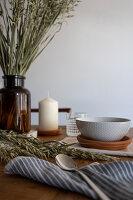 Gedeckter Tisch mit Kerze und Getreideähren in Apothekerflasche
