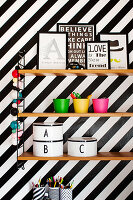 Shelves on black-and-white striped wall