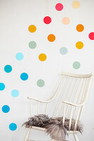 Fur rug on chair below multicoloured polka dots on wall