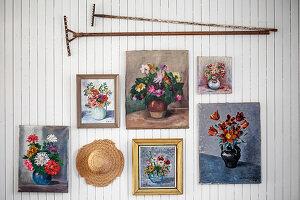 Blumenbilder, Vintage Rechen und Hut an weiß gestrichener Holzwand
