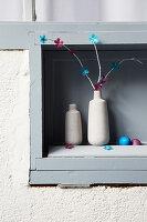 Zweige mit Papierblüten dekoriert in einer Vase