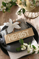 Sign reading 'Herbst' (autumn) and snowberries on plate