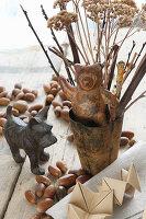 Tierfiguren aus Metall neben herbstlichen Zweigen und Eicheln