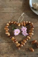 Herz aus aufgefädelten Eicheln und rosafarbene Chrysanthemen