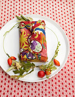 Gift wrapped in fabric with autumnal pattern on plate