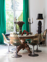 Round wooden table with carved base and classic chairs in front of window with green curtains
