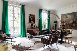 Braune Ledergarnitur und italienische Designerleuchte im Wohnzimmer, im Hintergrund Essbereicht mit großformatigem Gemälde