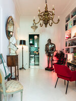 Bust on console table below mirror, suit of armour, shelves and upholstered chair in anteroom