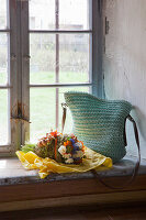 Crocheted bag and bouquet of flowers on sill of rustic window