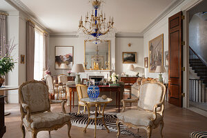 Pair of French gilded armchairs upholstered in elegant drawing room with Russian neo-classical ormolu and cut glass chandelier and faux zebra hide rug