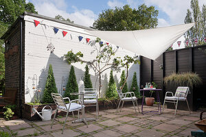 Chrome chairs and tables in paved garden with bunting and garden shade sail