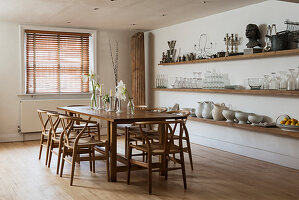 Large farmhouse dining table with wooden chairs in stylish dining room with open shelving