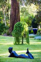 Liegende Frauenskulptur auf Rasenfläche, im Hintergrund japanische Hängelärche (Larix decidua 'Pendula') im Garten