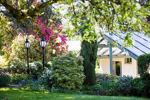 Sommerlicher Garten mit Laternen, Blick auf Haus