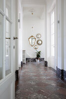Collection of mirrors in hallway with chequered marble floor