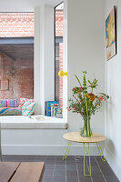 Vase of flowers on round three-legged table next to window seat in bay window