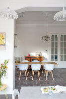 Shell chairs at wooden table in dining room of period building with stucco ceiling