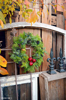 Door wreath with red apples, bound from mixed coniferous green