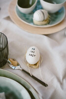 Easter egg decorated with lettering on set table