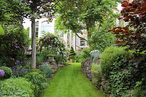 Lawn path between natural stone walls