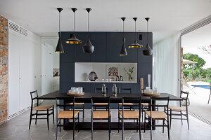 Schwarzer Esstisch mit Stühlen vor Raumteiler und offener Terrassentür