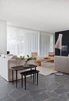 Helle Polstergarnitur und schwarze Beistelltische in offenem Wohnraum