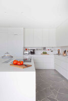 White fitted kitchen with island counter and stone worksurfaces
