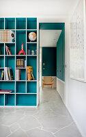 Türkisblaues Einbauregal neben Durchgang im Zimmer mit Natursteinplatten