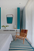 White bedroom with turquoise accents and chair next to window with floor-length curtains
