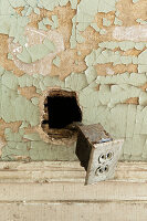Old power socket hanging out of wall with peeling paint