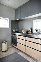 Kitchen counter with pale wooden fronts and grey wall units