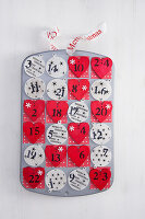 A homemade advent calendar made from a muffin tin
