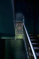 Dunkler Treppenaufgang mit antikem Geländer