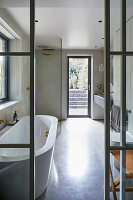 Door in glass and steel wall leading into pale grey bathroom