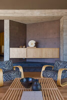 Zebra-patterned armchairs in living room with concrete walls