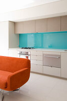 Orange sofa in front of modern open-plan kitchen