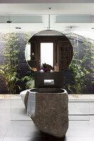 Waschbecken aus Basalt und Wandspiegel vor Glaswand