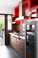 Küchenzeile mit Holzfronten und Einbaugeräten, darüber rotes Regal als Raumteiler