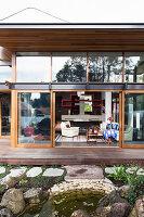 Wohnhaus mit Glasfassade, Blick vom Garten über Terrasse ins Wohnzimmer