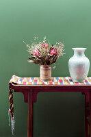 Konsole mit Tischläufer, Vase und Blumenstrauß vor grüne Wand