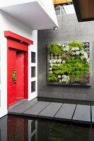 Eingangsbereich mit roter, chinesischer Tür und vertikaler Bepflanzung