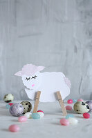Lamb made from paper and clothes pegs amongst Easter eggs