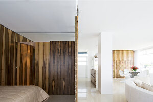 Sliding wooden screens around sleeping area with white designer sofa and dining area in background