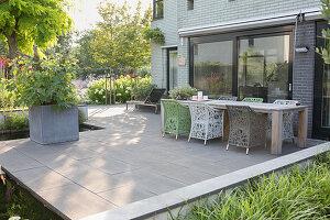 Holztisch und Designerstühle auf Terrasse mit Betonfliesen