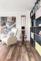 Sessel und modernes Sportgerät vor dem Wohnzimmerregal